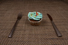 Fork, knife and a blue cupcake with cream. Breakfast sweet tooth. Denim, shiny cutlery, fresh cupcake with blue cream and confectionery Topping Stock Images