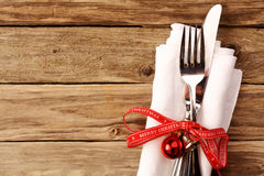 Fork and Knife with Christmas Decoration on Table. Tied Fork and Knife with Christmas Ball and Bell Decoration on Top of White Napkin, Placed on a Wooden Table stock photo