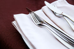 Fork and knife close up on white napkin. Royalty Free Stock Images