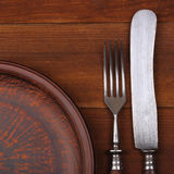 Fork, knife and dinner plate  on a  wood background Royalty Free Stock Photos
