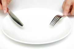 Fork and a knife with empty dish Royalty Free Stock Photos