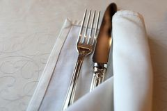 Fork and knife. In napkin on table stock images