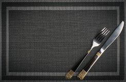 Fork and Knife with golden elements on a placemat. Metal Fork and Knife with golden elements on a placemat, top view with text space stock photo