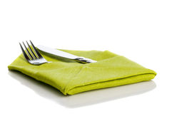 Fork and knife in green cloth. Fork and knife wrapped in green cloth for table setting isolated on white background stock photography
