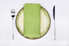 Fork, knife and green napkin on green plate Royalty Free Stock Images