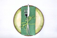 Fork, knife and green napkin on green plate Royalty Free Stock Photo