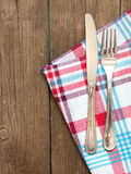 Fork and knife on kitchen towel and old wooden table Royalty Free Stock Image