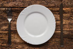 Fork and knife lying near empty white plate Stock Photo