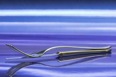 Fork and knife on the blue. Fork and knife on a metallic surface that reflects his inverted figure, all in the blue stock photos