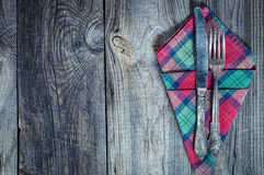 Fork and knife on a napkin, gray old wooden table. An empty space on the left Royalty Free Stock Photos