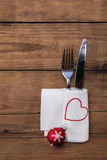 Fork and knife with napkin and red white christmas ball on old w Royalty Free Stock Photos