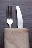 Fork and knife in napkin on table Stock Images