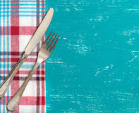 Fork and knife on napkin on turquoise wood. Fork and knife on napkin on a turquoise wood Royalty Free Stock Image