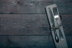 Fork and knife in napkin on wooden background. Toned Royalty Free Stock Images