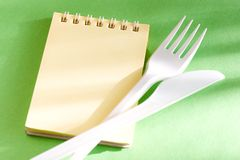 Fork, knife and notepad Stock Photos
