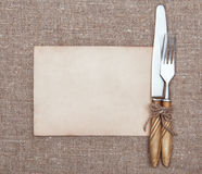 Fork, knife and old paper on the burlap Stock Photos