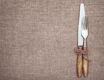 Fork, knife and old paper on the burlap Royalty Free Stock Image