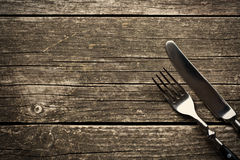 Fork and knife on old wooden table Royalty Free Stock Photos
