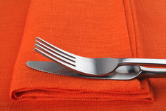Fork and knife on orange napkin and tablecloth. Stock Image