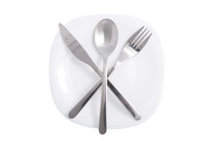 Fork and knife over white plate isolated Royalty Free Stock Image