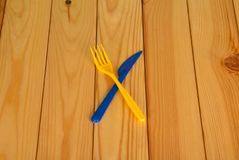Fork and knife, plastic disposable devices, on wooden table Stock Photo