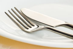 Fork and knife on plate Royalty Free Stock Photography