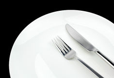 Fork, knife and plate on a black background Royalty Free Stock Photo