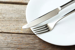 Fork, knife and plate on a grey wooden background Royalty Free Stock Image