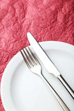 Fork, knife and plate on the red background Royalty Free Stock Image