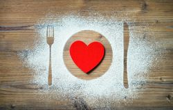 Fork, knife and plate with red heart, flour sprinkled around the Stock Image