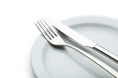Fork, knife and plate on a white background Royalty Free Stock Photo