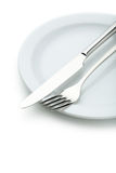 Fork, knife and plate on a white background Stock Photos