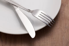 Fork and knife on plate Royalty Free Stock Photo