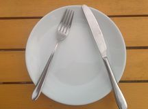 Fork and knife on plate stock image