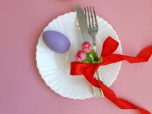 Fork, knife with red bowknot, colored egg on white plate on pink background. Easter place setting on pink background. Fork, knife with red bowknot, colored egg royalty free stock photo
