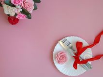 Fork, knife with red bowknot, marzipan rose, white plate on pink background. Romantic place setting on pink background. Fork, knife with red bowknot, marzipan royalty free stock photography