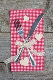 Fork, knife on red checkered napkin and wooden hearts Stock Photography