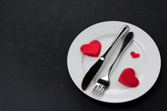Fork, knife and a red heart on a plate Stock Photography