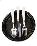 Fork, knife and spoon on a black plastic plate Royalty Free Stock Photo