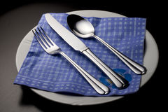 Fork, knife and spoon on a blue napkin. On a white plate. Picture taken in studio Stock Photography