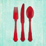 Fork, knife and spoon cutlery in red on turquoise wood background royalty free stock photography