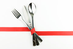Fork, knife and spoon tied up with red ribbon Stock Photos