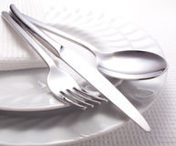 Fork, knife, spoon and a white plate Royalty Free Stock Photography