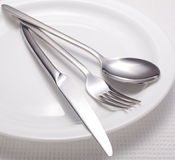 Fork, knife, spoon and a white plate Stock Image