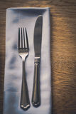 Fork and knife on a table, on a napkin Royalty Free Stock Images