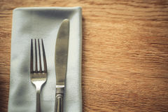 Fork and knife on a table, on a napkin Royalty Free Stock Photography