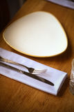 Fork and knife on a table, near a plate. Stock Photo