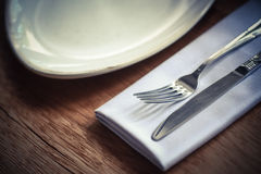 Fork and knife on a table, near a plate Royalty Free Stock Images