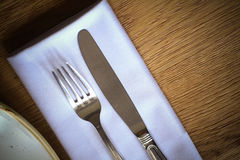 Fork and knife on a table, near a plate Stock Images