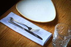 Fork and knife on a table, near a plate Stock Photo
